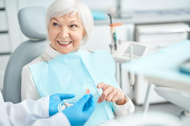 Dame wird beraten am Zahnarzt-Stuhl